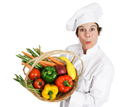 sourced: Female chef holding a basket of fresh organic, locally sourced vegetables.  Isolated on white.