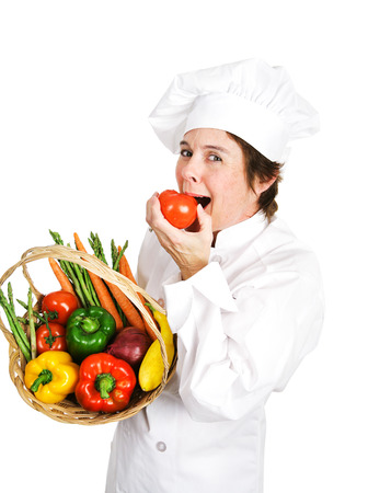 Chef holding a basket of fresh vegetables takes a bit out of a ripe tomato.  Isolated on white. photo