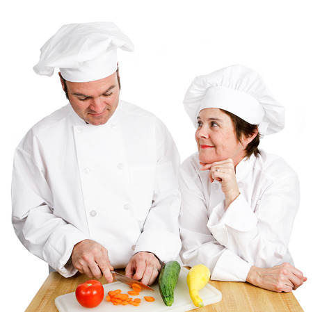 observes: One chef observes anothers prep work, chopping vegetables.  Isolated on white.