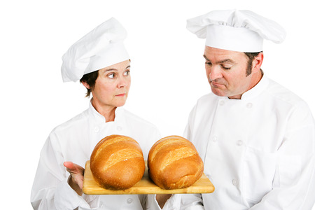One baker evaluates another bakers fresh Italian bread.  Isolated on white.