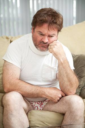 Injured man wearing a neck brace, suffering from depression, home alone in his underwear. Stock Photo