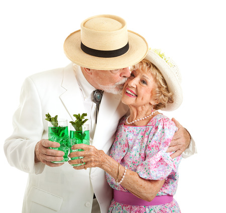 kentucky derby: Southern senior couple dressed for the Kentucky Derby,  holding mint juleps and kissing. Stock Photo