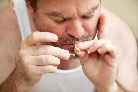 wifebeater: Uomo che fuma pentola, accendendo una joint con un fiammifero.