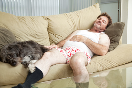 underpants: Unshaven middle-aged man asleep on the couch with his dog.