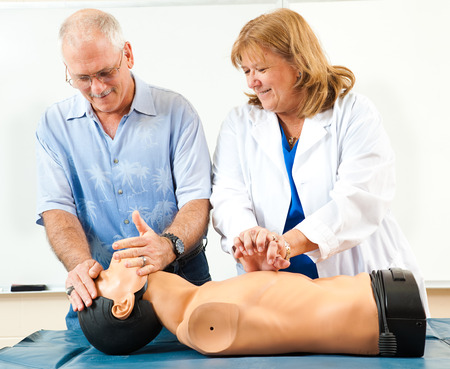 chest compression: Doctor teaching CPR to a mature student. Stock Photo