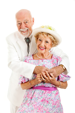 Portrait of an elderly couple with the husband embracing his beautiful wife.  Isolated on white.