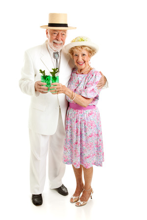 Senior couple dressed up for the Kentucky Derby, drinking mint juleps.  Full body isolated on white. photo