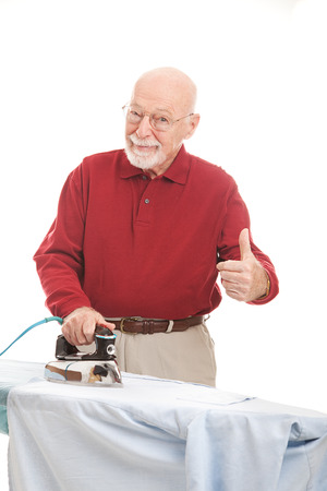 Senior man doing his own ironing and giving a thumbs up sign.  Isolated on white. photo