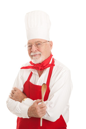 Experienced older chef holding a wooden spoon.  Serious expression, isolated on white.