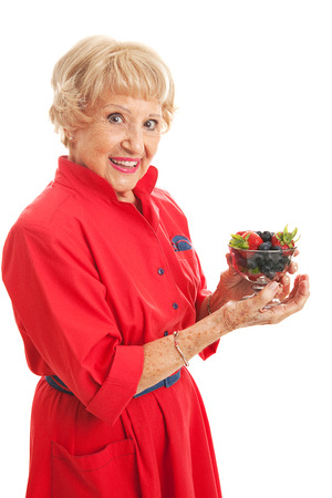 snacking: Fit senior woman snacking on a bowl of healthy mixed berries.  Isolated on white. Stock Photo