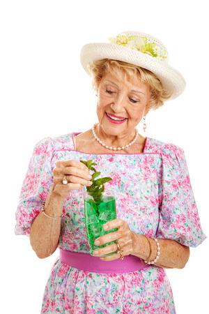 kentucky derby: Southern senior lady dressed for the Kentucky Derby and drinking a mint julep.  Isolated on white.