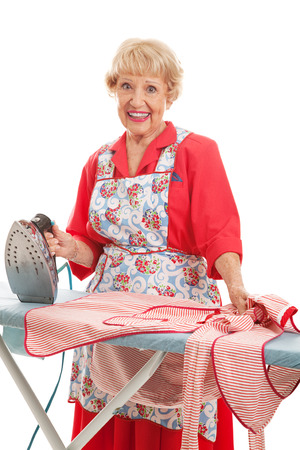 Sweet old lady in retro apron doing the ironing.  Isolated on white.