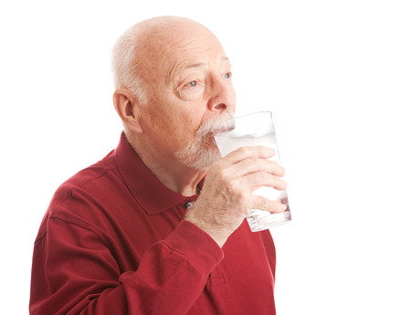 Senior man quenches his thirst with a big glass of filtered ice water.  White Background. photo