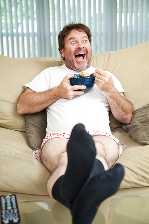 Middle-aged man in his underwea watching TV and eating cereal.  Hes laughing at whats on television.