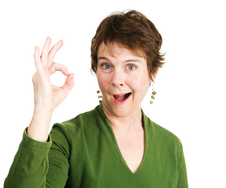 irish ethnicity: Pretty, mature woman with a pixie cut smiles and gives the Okay hand sign.  Isolated on white. Stock Photo