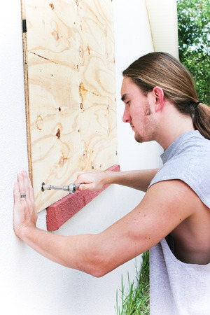 Young man boarding up windows to prepare for natural disaster such as hurricane or tornado. Standard-Bild