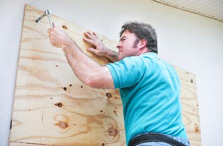 Man Einsteigen die Fenster auf seinem Haus, um für einen Hurrikan oder Tornado vorzubereiten.