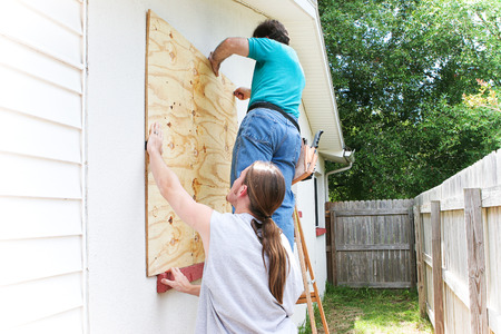 Teenage son helping his father board up the windows of their house in preparation for a hurricane or tornado. Stock Photo