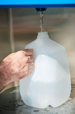 jug: Closeup of a mans hand filling a gallon jug from a water machine. Stock Photo