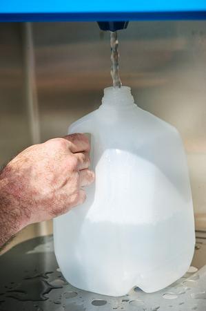 Gros plan de la main d'un homme de remplir un récipient d'un gallon d'une machine à l'eau. Banque d'images - 39785456