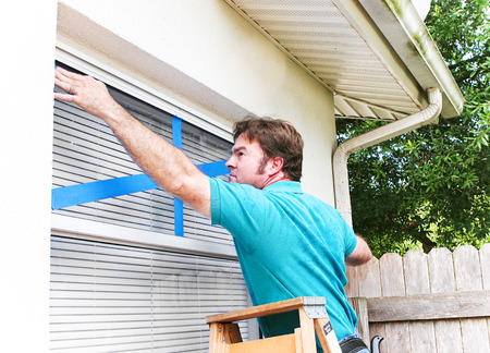 windows: Man taping the windows on his home to protect from broken glass in a hurricane.