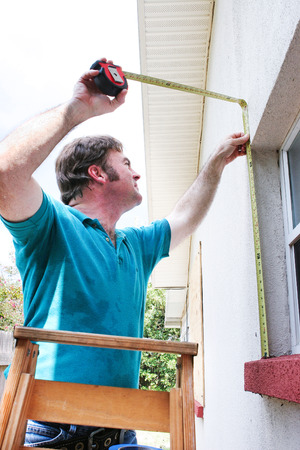 windows: Contractor measuring windows for hurrican shutters to replace plywood. Stock Photo