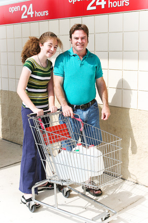 Father and teenage daughter shopping for water in preparation for a drought, hurricane, or other disaster.