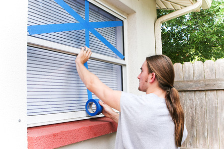 taping: Young man taping up windows in preparation for a hurricane.