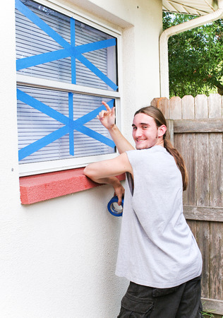 Young man pointing to windows he has taped up to prepare for a hurricane. photo