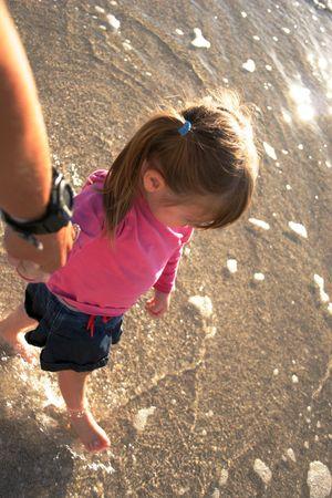 toddler walking: toddler walking in surf Stock Photo