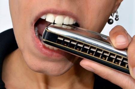 nota: a woman playing harmonica on white background