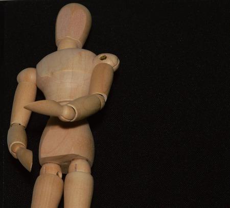 marioneta de madera: una marioneta de madera colocado delante de un fondo negro Foto de archivo