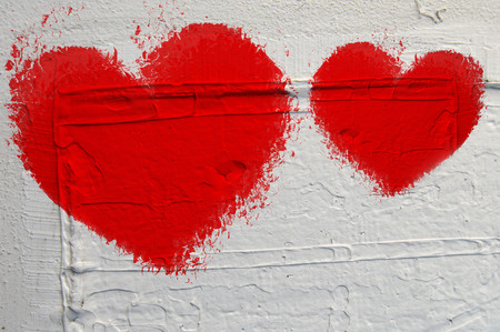crumbling: red heart painted on white wall with crumbling plaster