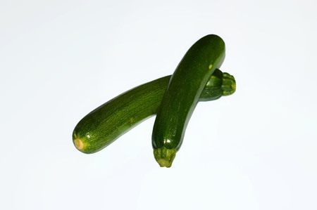 pair of green zucchini on white background