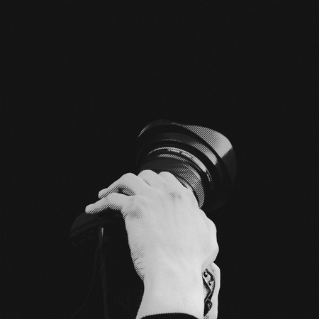 photomontage: photomontage, camera with two hands on black background