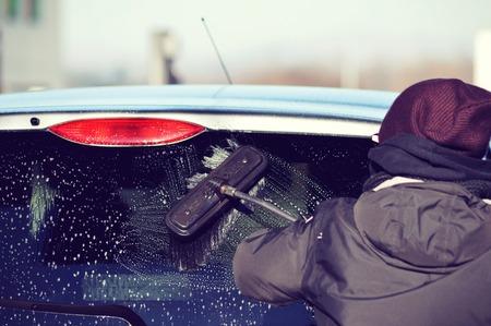 lavado: persona que lava un coche con un cepillo Foto de archivo