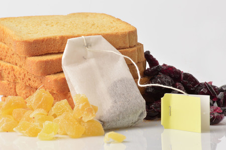 nourish: Group of rusks, berries, ginger and a tea bag on white background