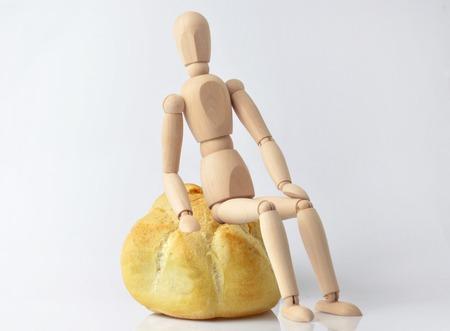 marioneta de madera: Individual marioneta de madera que se sienta en un bollo en un fondo blanco Foto de archivo