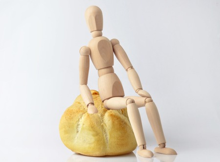 marioneta de madera: Single wooden puppet sitting on a bun on a white background