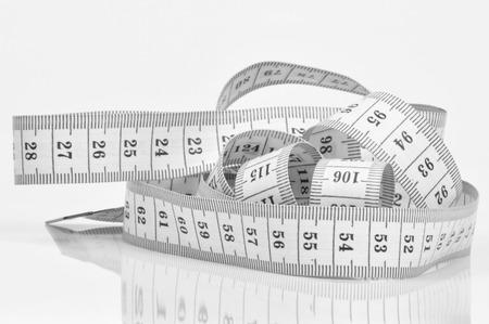 cinta de medir: cinta métrica con sencillo en el fondo neutro Foto de archivo