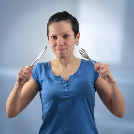girl with knife: girl with knife and fork on a neutral background