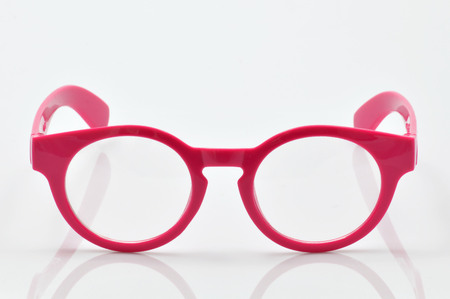 testing vision: glasses with pink frames on neutral background