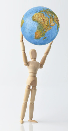 foreign land: isolated mannequin with globe on a neutral background