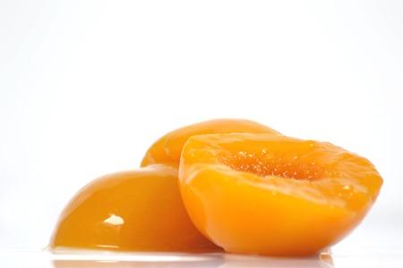 jarabe: melocotones en almíbar sobre un fondo blanco