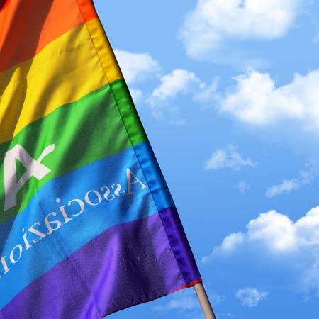 transexual: bandera del arco iris sobre el cielo azul con nubes blancas Foto de archivo