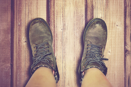 leather boots: feet with leather boots on wooden surface Stock Photo