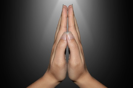 hands clasped in prayer on a black background