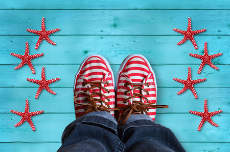 shoes with red and white stripes, with starfish and sea shells, on wooden background