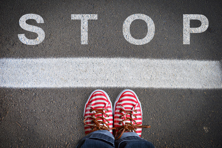 person with sneakers standing on the asphalt, in front of the stop message