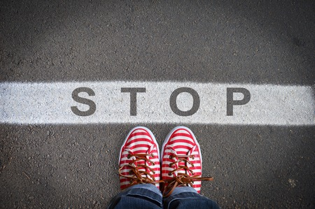 street wise: person with sneakers standing on the asphalt, in front of the stop message